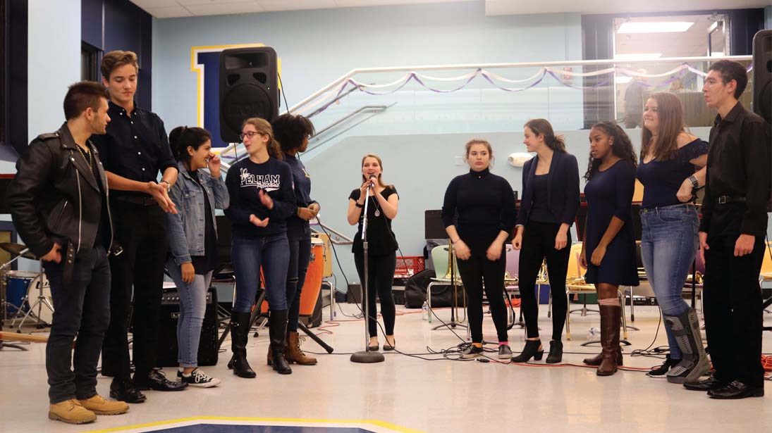 The Acapelicans warm up in Cafeteria C before their premiere performance at the stage band fundraiser on November 8.