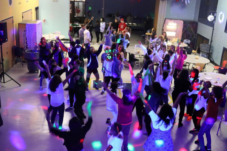 Freshmen dance in Cafeteria C, illuminated by black light and glow sticks.