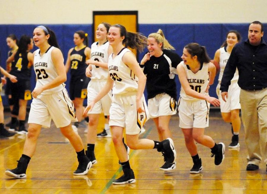 The girls basketball team runs onto the court for their game against Walter Panas.