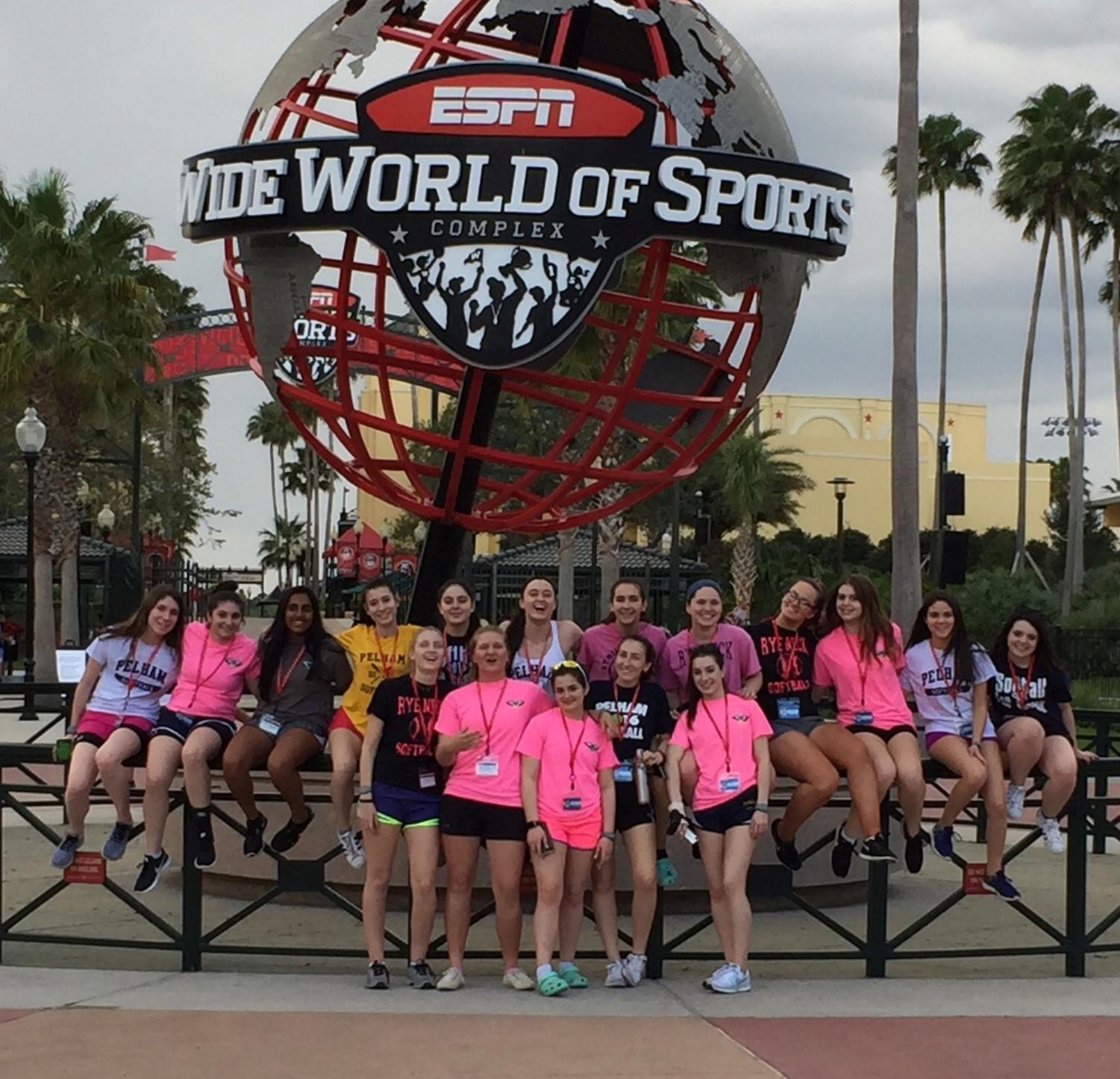 The varsity girls softball team gathers in front of the sports complex at Disney World.