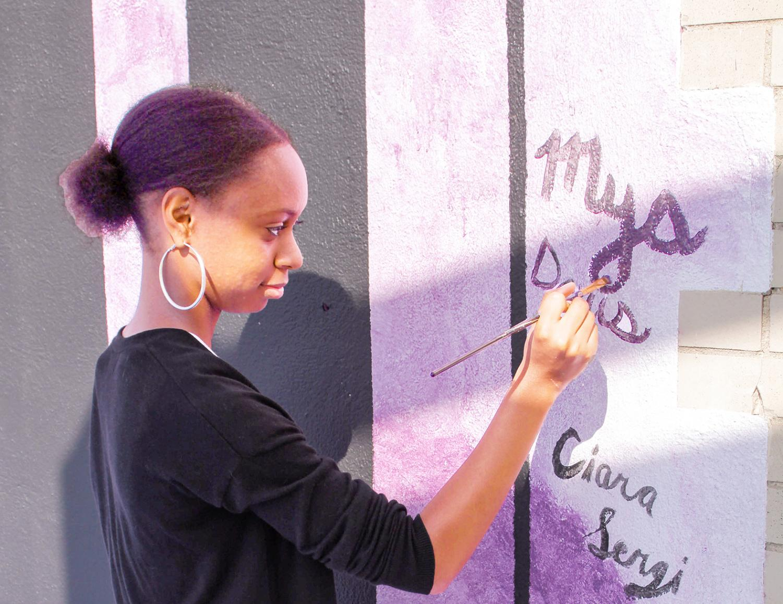 Sophomore Mya Davis signs her name to her award-winning mural.
