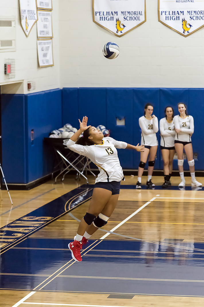 Senior Nora Tahbaz jumps high in the air to serve the ball.