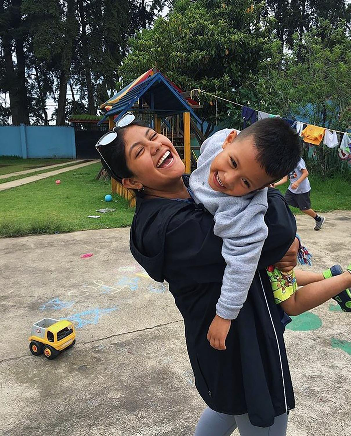 Senior Gabby Hood plays with kids in  Guatemala.