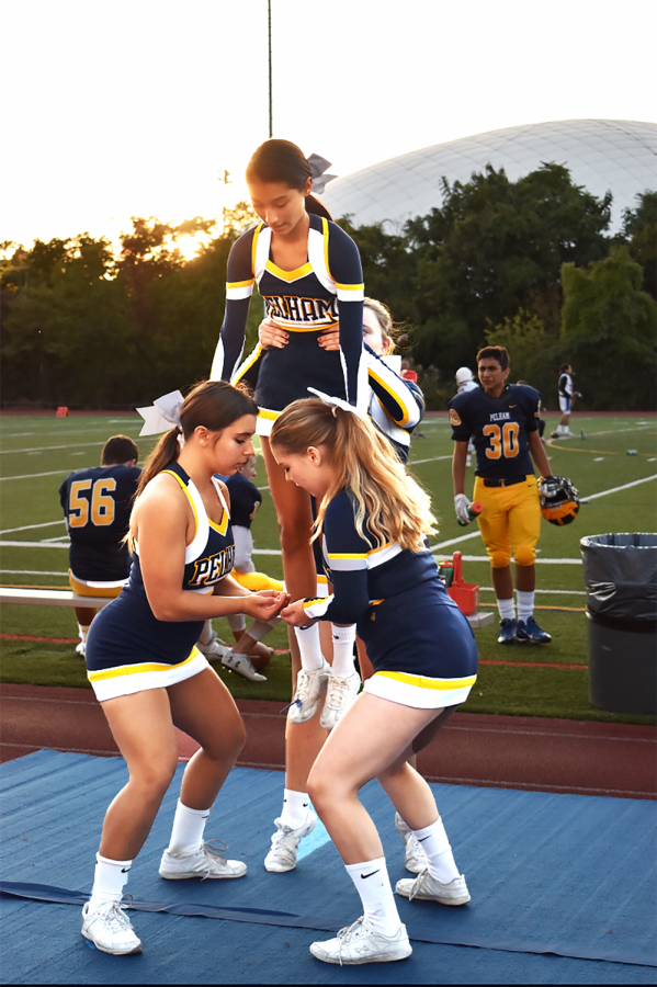 Teammates lift senior Kim Perez at the Homecoming football game.