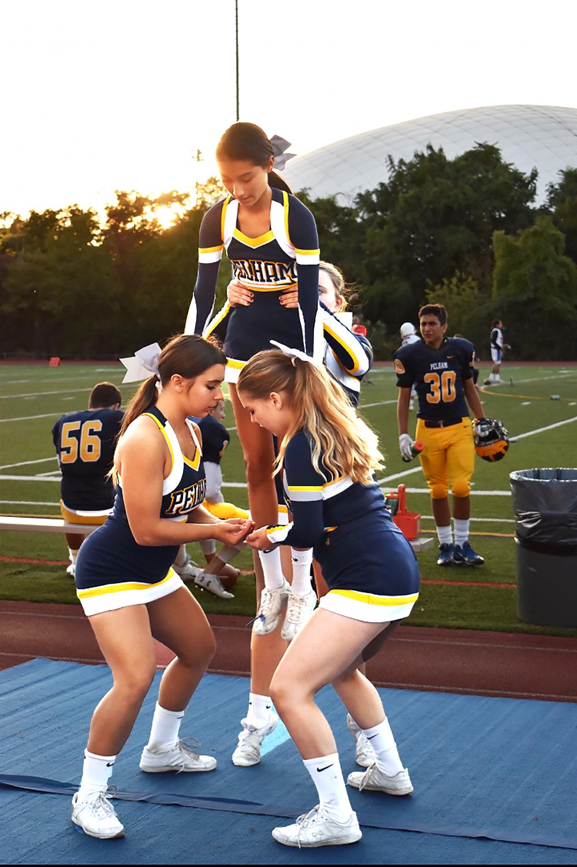 Teammates lift senior Kim Perez at the Homecoming football game.