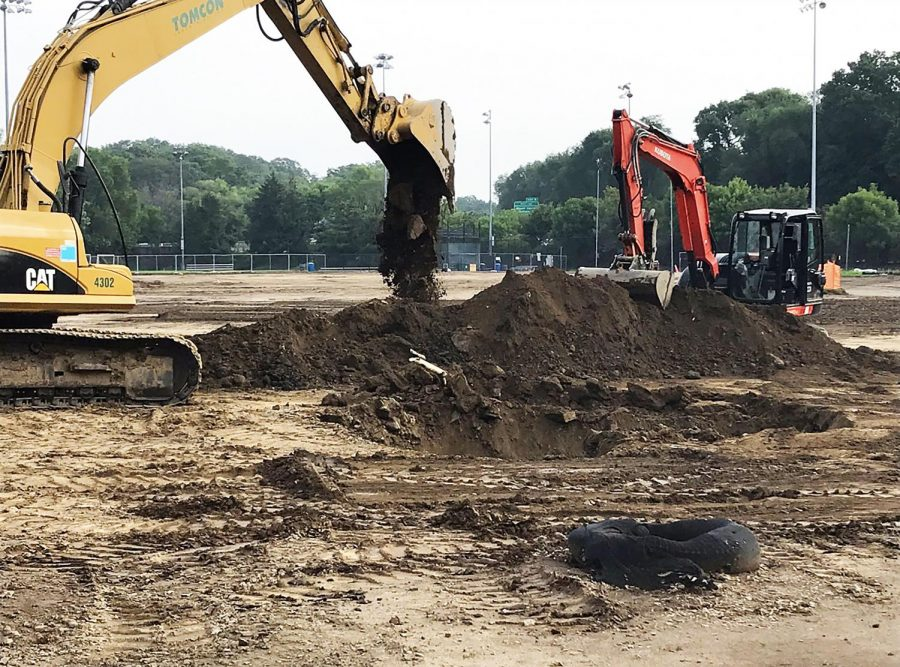 At the construction site of the baseball field an excavator clears ground.