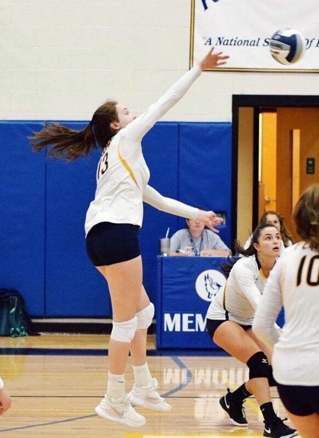 Senior Grace Aronson spikes the ball over the net at the opposing team.