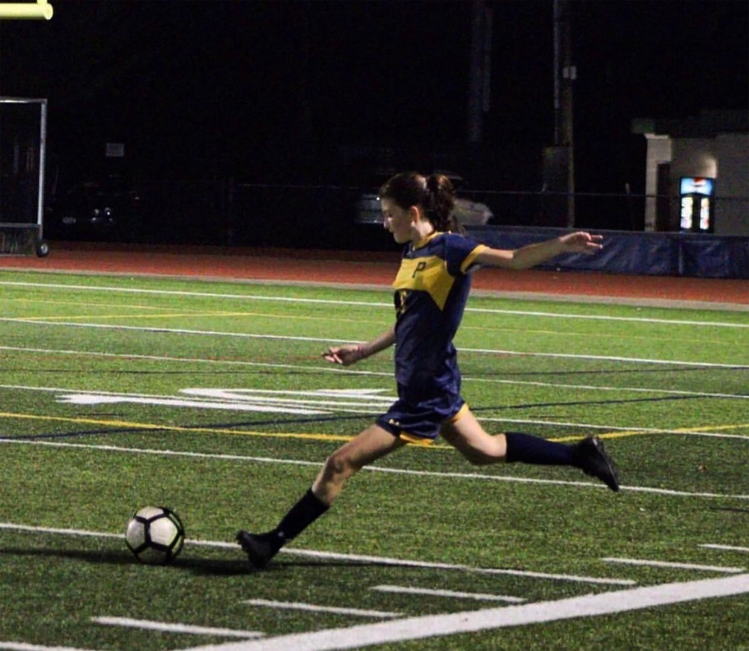 Junior Catie Woods boots the ball across the field.