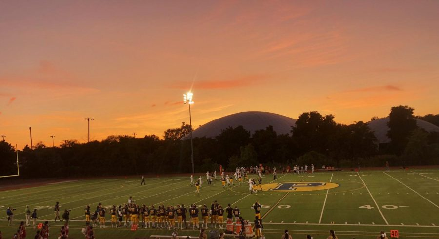 The Pelham varsity football team drives down the field as the sun sets over Glover Complex.