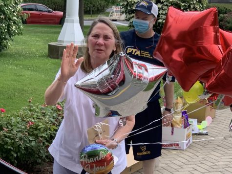 With Teachers Union president Mark Finegan just behind her, Mrs. Clark waves to well-wishers as they hand her goodbye balloons.