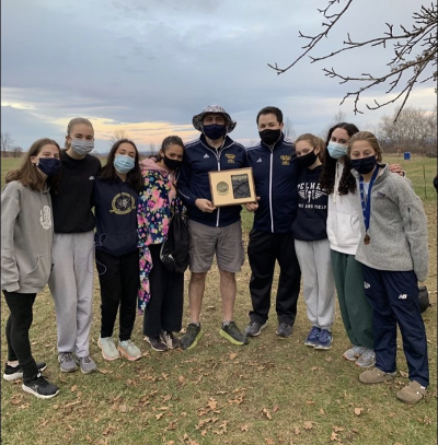 The girls varsity Cross Country team shares their league title victory with their coaches.