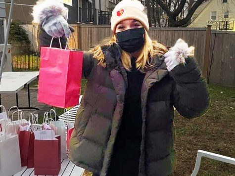 A masked club member shows of a bag of goodies, destination --  Bayberry Care Center.