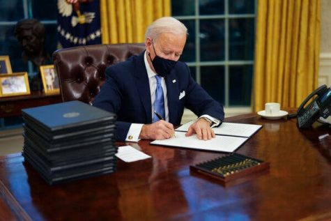 President Biden signs an executive order as he gets to work pushing his agenda on the environment and other issues.