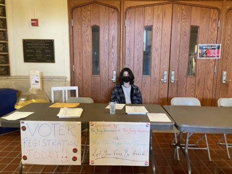 Manning the table during a free period, junior James Findikyan helps students sign up to perform their civic duty.